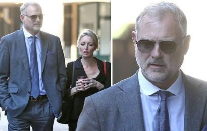 John Leslie looks sombre as he arrives at court after being charged with sexual assault